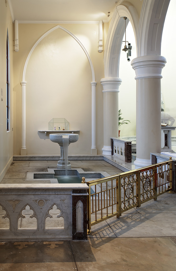 The baptismal font receives ample window light in the day, and is accented for drama at night.