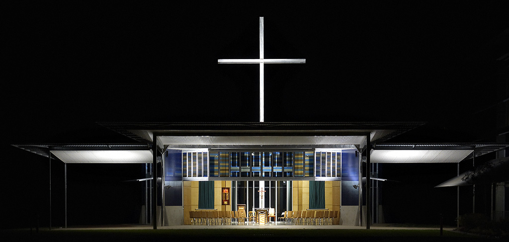 great cross in industrial galvanised steel rises above the chapel