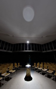 A single narrow spotlight on the baptismal font reflects as a 'moon' on the ceiling.  Disturbing the water creates fluid patterns of light.
