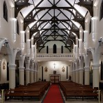 Narrow-beam uplighting of the piers and ceiling lends a festive feel to the nave.