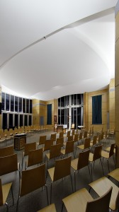 Before and after mass, the chapel is brightly lit mainly with indirect uplighting.  This 'opens' the relatively small space with soft light and provides a social atmosphere.   The font is spot-lit as a focal point; as are the altar and processional cross.